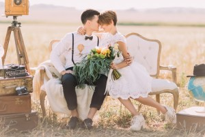 The lovely close-up horizontal portrait of the newlyweds sitting head-to-head on the sofa. The bride is holding the colourful wedding bouquet at the background of the field