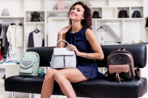 Portrait of young smiling brunette picking a new handbag while sitting on a bench looking at camera in clothing store